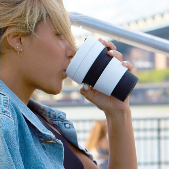 A girl drinks from the Stojo Collapsible Pocket Cup Black