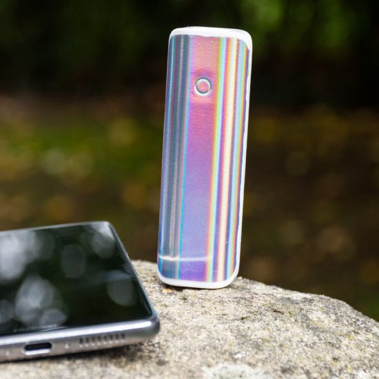 Iridescent Power Bank 2200mAh looks super shiny on a rock next to a smartphone