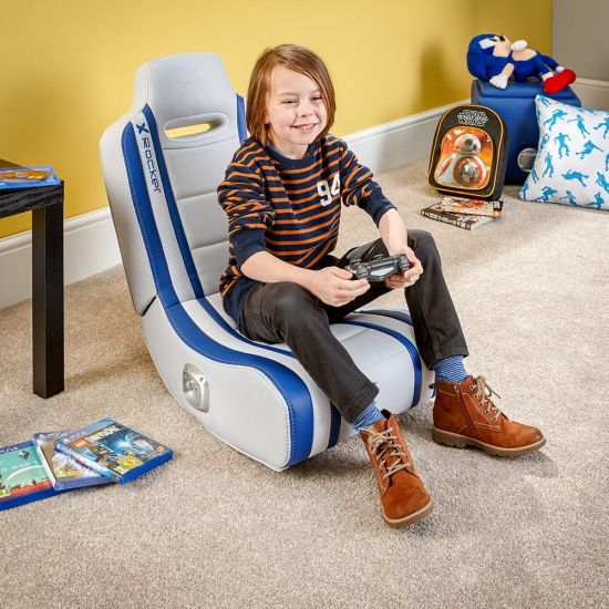 young boy sat on x-rocker shadow blue gaming chair playing on playstation