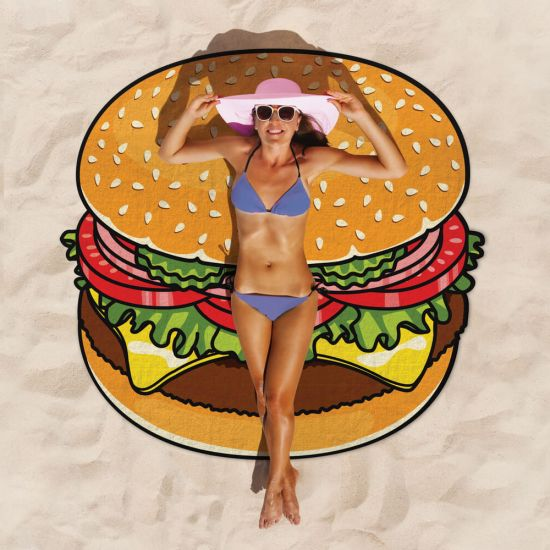 A girl in a bikini and sun hat relaxes on the Giant Burger Beach Blanket on a sandy beach