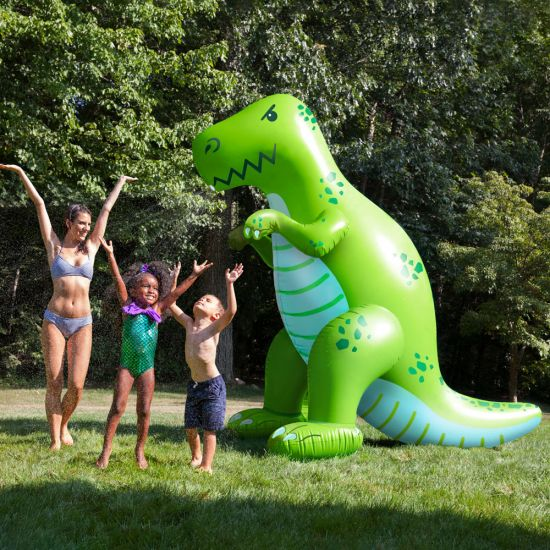 A family play under the water spray of the Giant Inflatable Dinosaur Garden Sprinkler