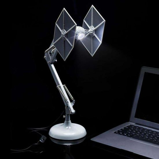Star Wars TIE Fighter Posable Desk Lamp lights up a dark desk and a laptop