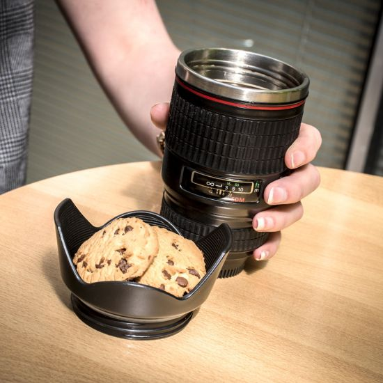 Cookies sit in the tray of the Camera Lens Mug with Twist-Off Lid as a hand holds the cup