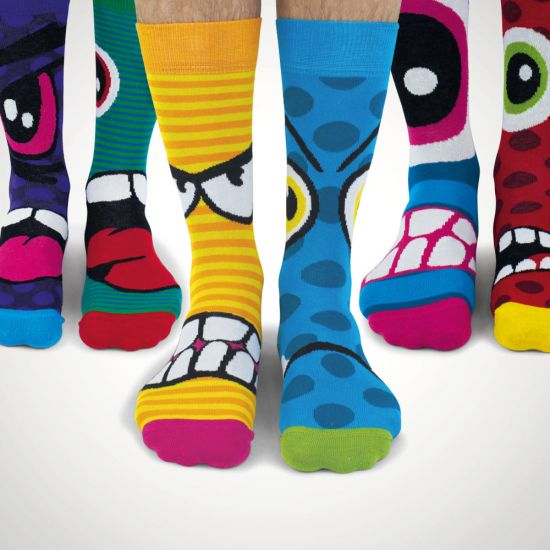 United Oddsocks – Stress Head Socks - Three pairs of odd socks with angry faces on a grey background