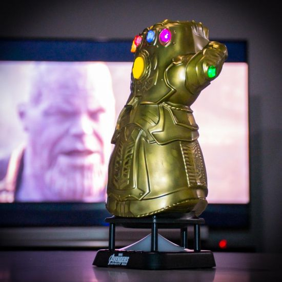 Avengers Thanos Infinity Gauntlet Bluetooth Speaker with infinity war on the TV behind