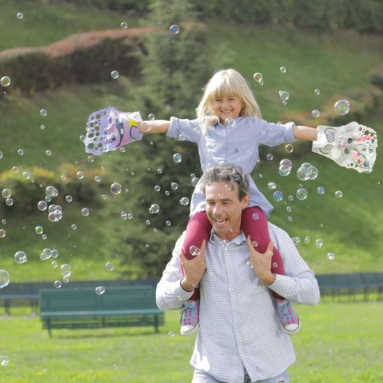A girl has fun creating hundreds of bubbles with the Glove a Bubbles on her Dad's shoulders