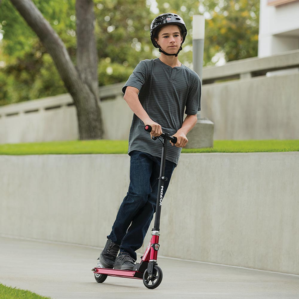 teenager on electric scooter on pavement